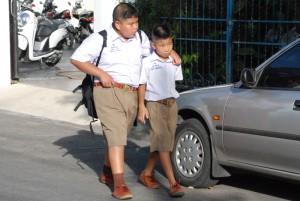 Zwei Freunde in Schuluniform auf dem Heimweg. Hier mal in hellbraunen Hosen.