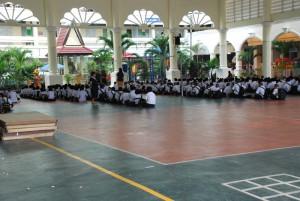 So ordentlich und so brav sitzen Schüler – hier in der seitlich offenen Sporthalle der Schule.